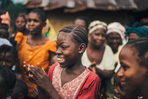 A crowd of African woman, focusing on one woman who is smiling and clapping.